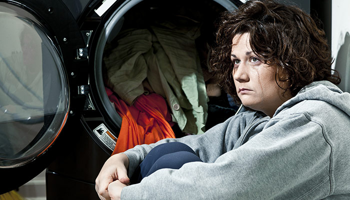 Picture Of Woman Crying In Front Of Her Front Load Washer
