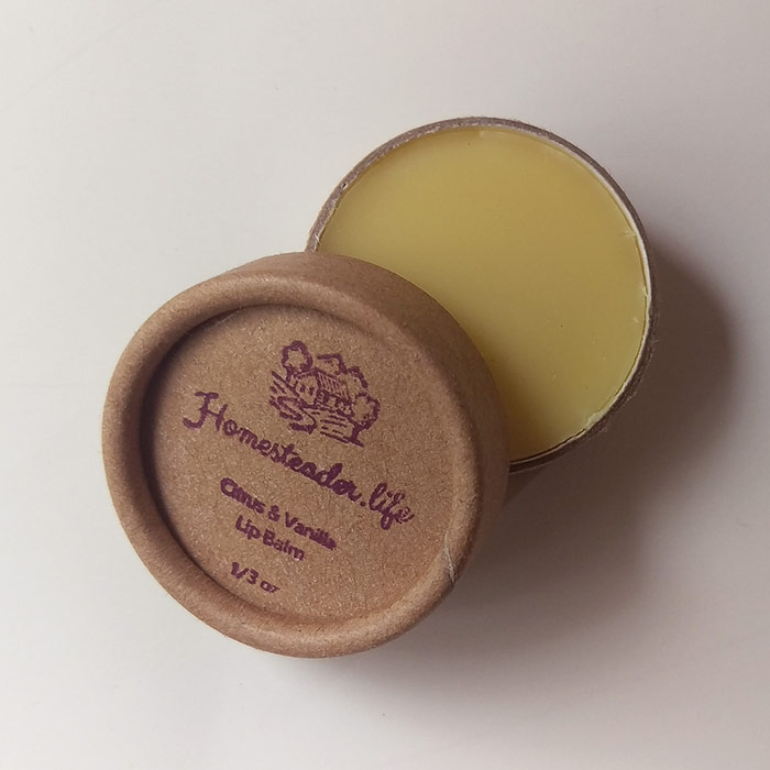 Citrus And Vanilla Lip Balm In Kraft Container With Lid Overlapping Jar